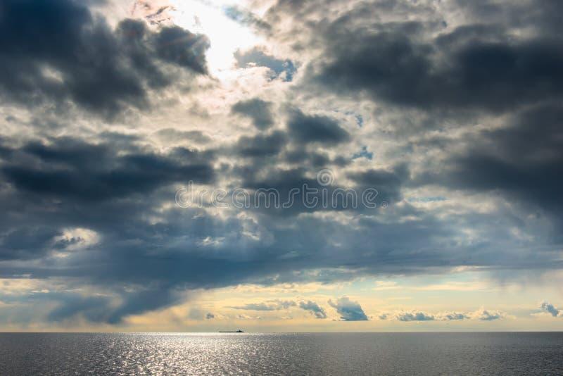 Dunkle Kumuluswolken, die über Meer schweben stockfotografie