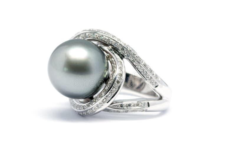 Dunkle Perle mit dem Diamant- und Goldplatinring lokalisiert lizenzfreie stockfotografie