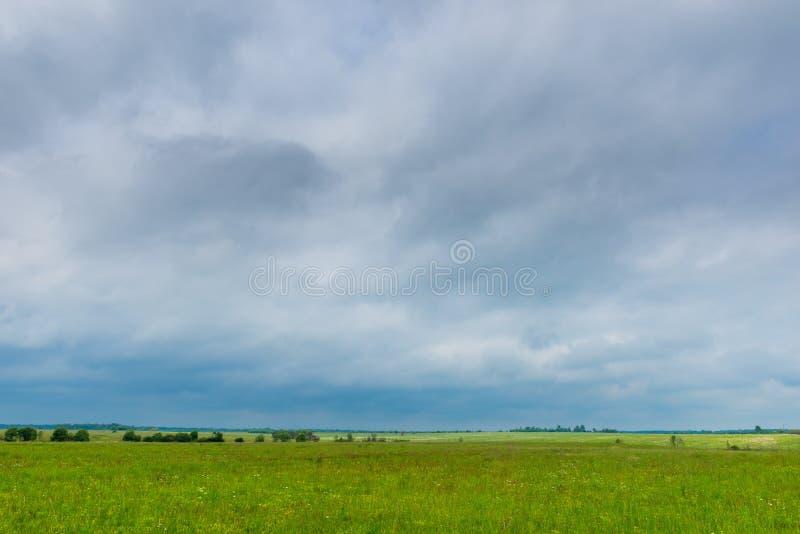 Dunkle regnerische Wolken hängen an einem grünen Frühlingsfeld stockfotos