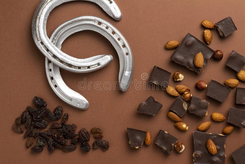Dunkle Schokoladenstücke mit gebratenen Mandeln und Rosinen zerstreuten herum lizenzfreie stockfotografie
