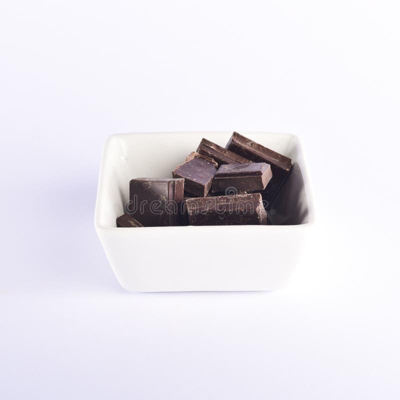 Dunkle Schokoladenstücke vereinbarten in einer Schüssel auf einem weißen Hintergrund lizenzfreie stockbilder