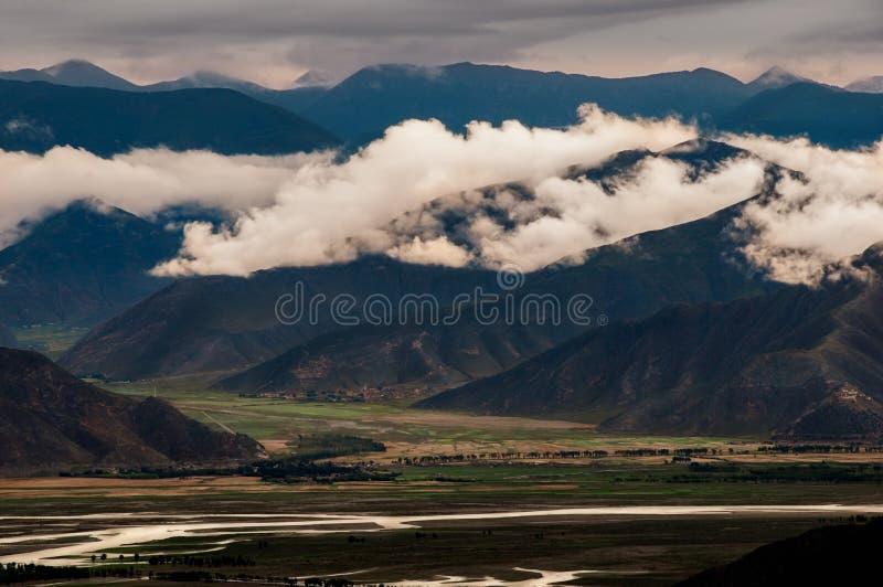 Dunkle schwermütige Landschaftsansicht von Bergen und von Hügeln in Tibet lizenzfreies stockbild