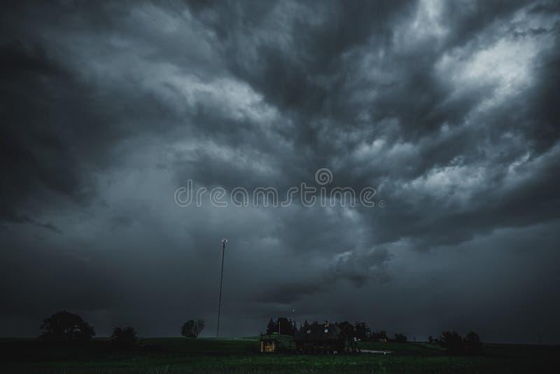 Dunkle stürmische Wolken und wenige Häuser auf dem Feld mit einem Funkturm stockfoto