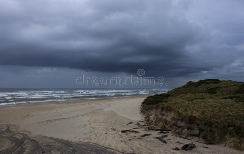Dunkle Sturmwolken über Ozean-Strand Tasmanien stockfotografie