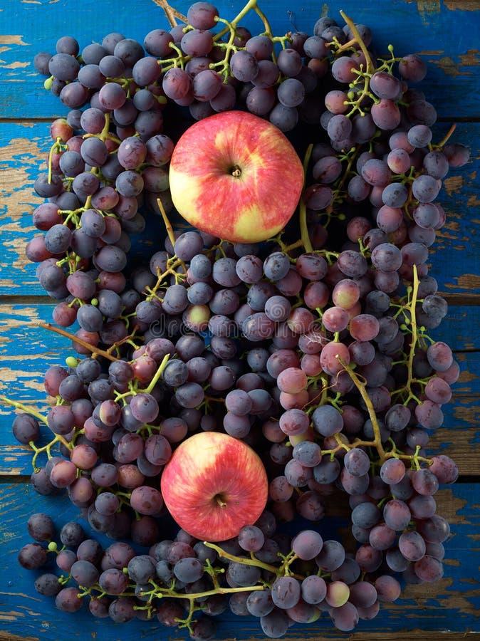 Dunkle Trauben und Äpfel stockfotografie