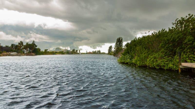 Dunkle Wolken, die über dem Wasser schweben stockfotos