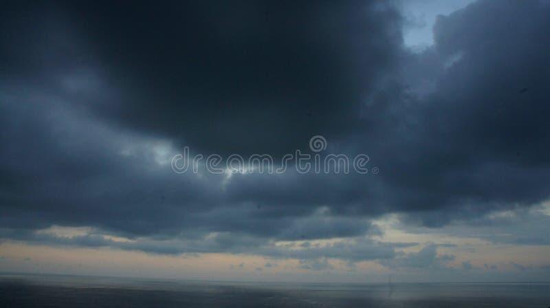 dunkle Wolkenversammlung über Meer stockfotografie