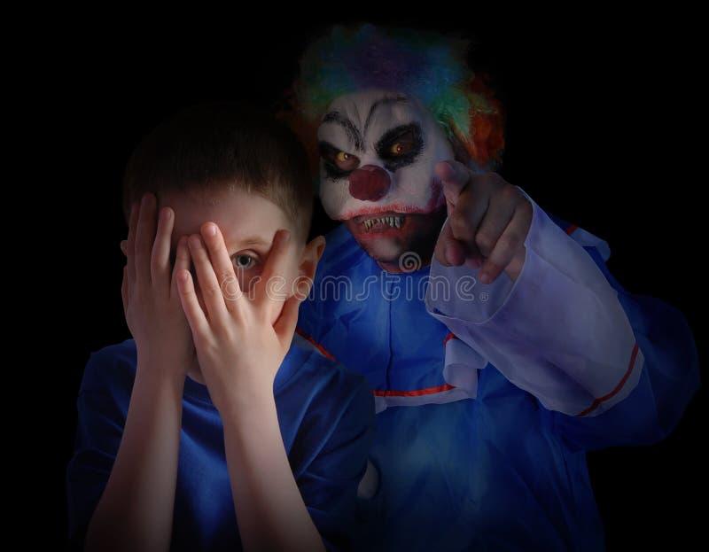 Dunkler furchtsamer Clown Looking am kleinen Kind lizenzfreies stockfoto