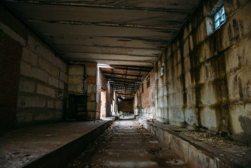 Dunkler furchtsamer Korridor in verlassener industrieller ruinierter Ziegelsteinfabrik, gruseliger Innenraum, Perspektive lizenzfreies stockbild