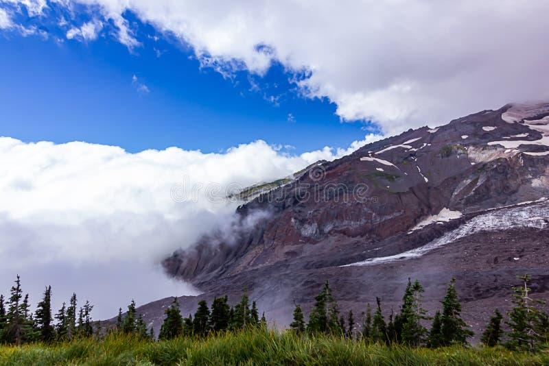 dunkler Hügel des purpurroten Bergabhanges nahe grünen Wiesen stockfotografie