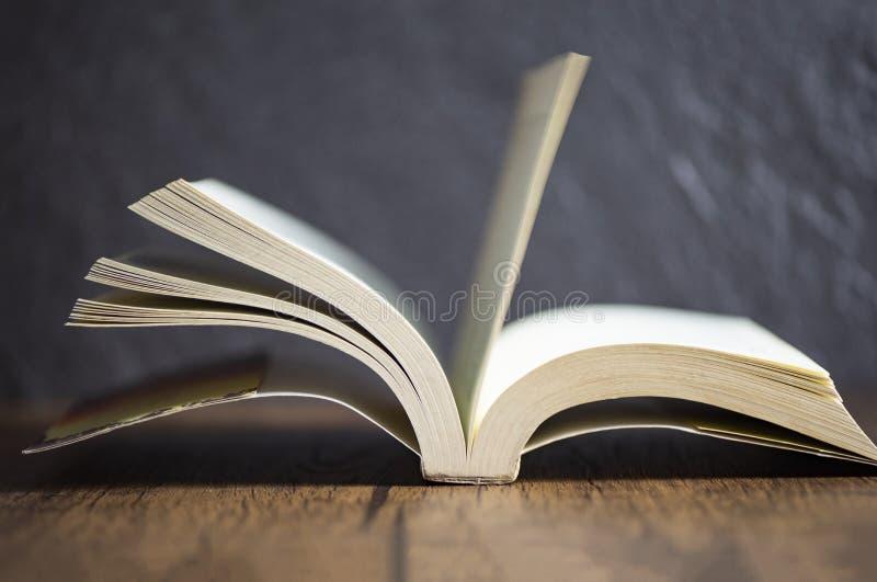 dunkler Hintergrund des alten Holztischs der Weinlese des offenen Buches am Bibliotheksausbildungskonzept lizenzfreies stockfoto