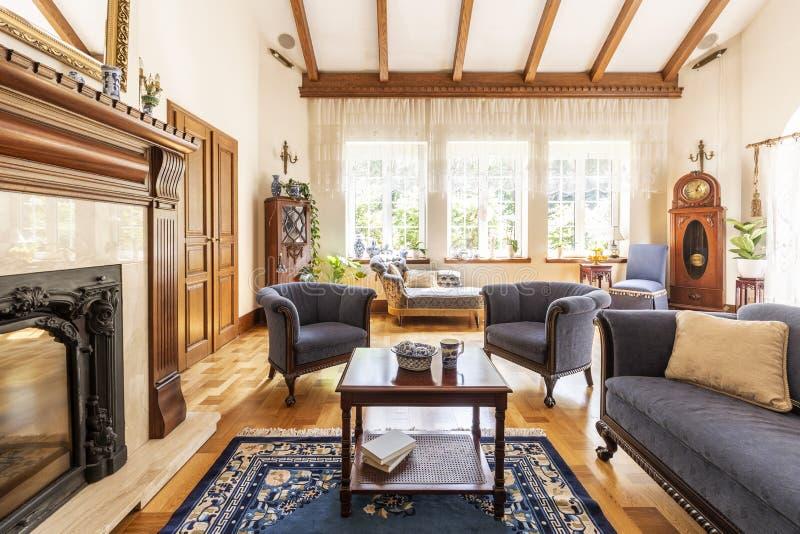 Dunkler Holztisch auf Teppich zwischen blauen Lehnsesseln und Sofa im Luxusinnenraum mit Kamin Reales Foto stockbilder