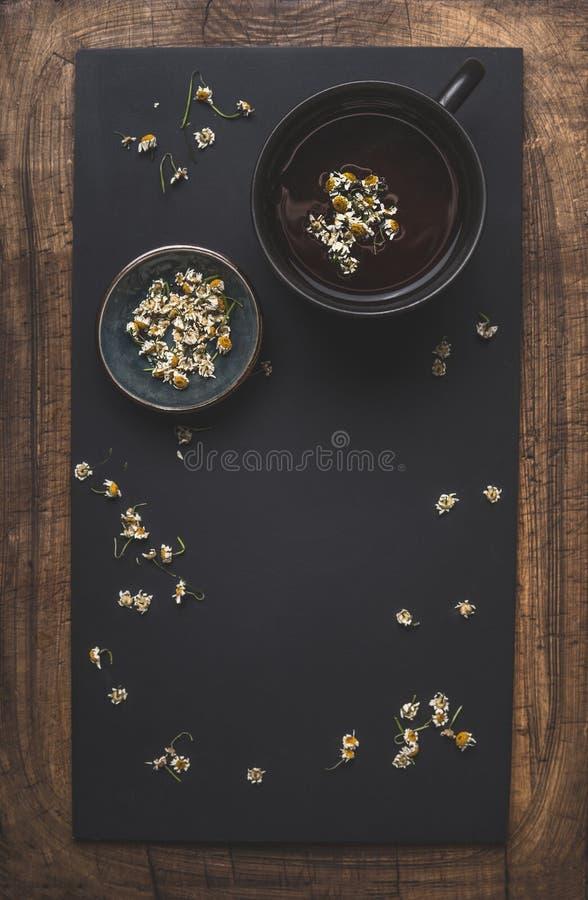Dunkler Kamillenteehintergrund mit Tasse Tee, getrocknete Kamillenblumen und Honig in der Schüssel, Draufsicht Feld Beheben Sie,  stockbilder