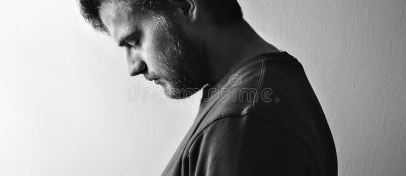 Dunkler Kerl, Mannprofil, kippte seinen Kopf unten in der Krise auf einem weißen Hintergrund, der lokalisiert wurde, Schwarzweiss stockfotos