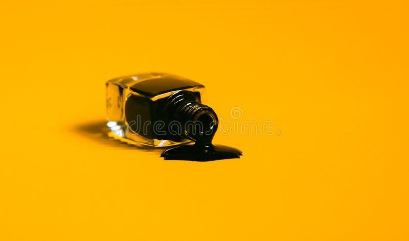 Dunkler Nagellack lief die Flasche ?ber Vibrierender orange Hintergrund stockfotos