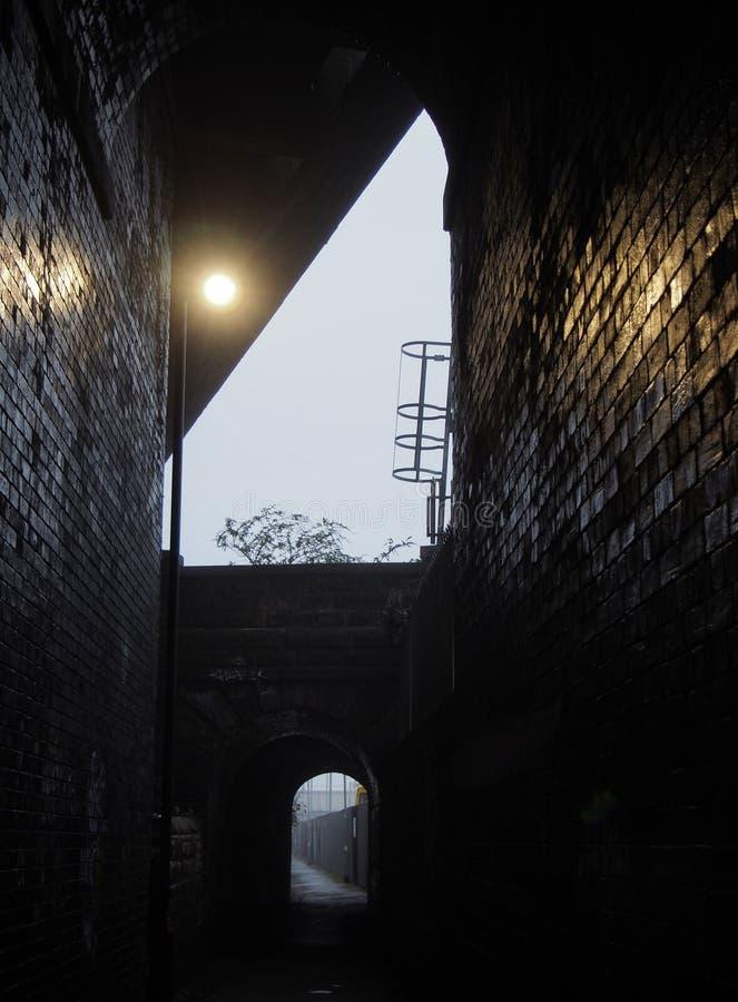 Dunkler Ziegelsteindurchgang unter einer alten Brücke mit einem kleinen gewölbten Eingang, der zu eine Gasse in der dunklen Glätt lizenzfreie stockfotografie