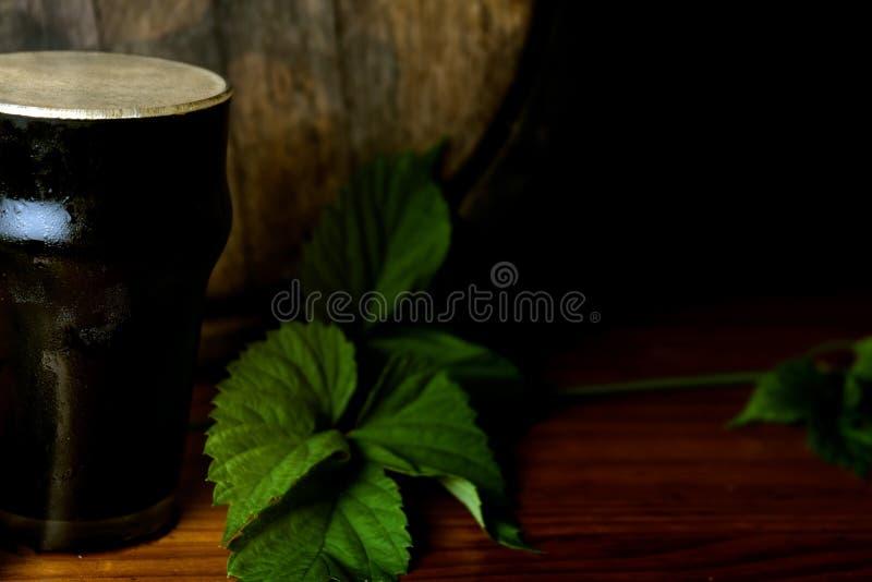 Dunkles Bier des halben Liters freundlich mit einem Blatt von Hopfen auf dem Hintergrund des Fasses Abschluss oben stockfotografie