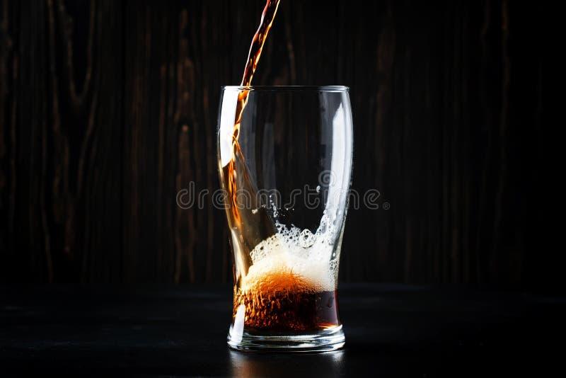 Dunkles englisches Bier, Ale oder Stout wird in Glas, dunkle Bar c gegossen lizenzfreie stockbilder