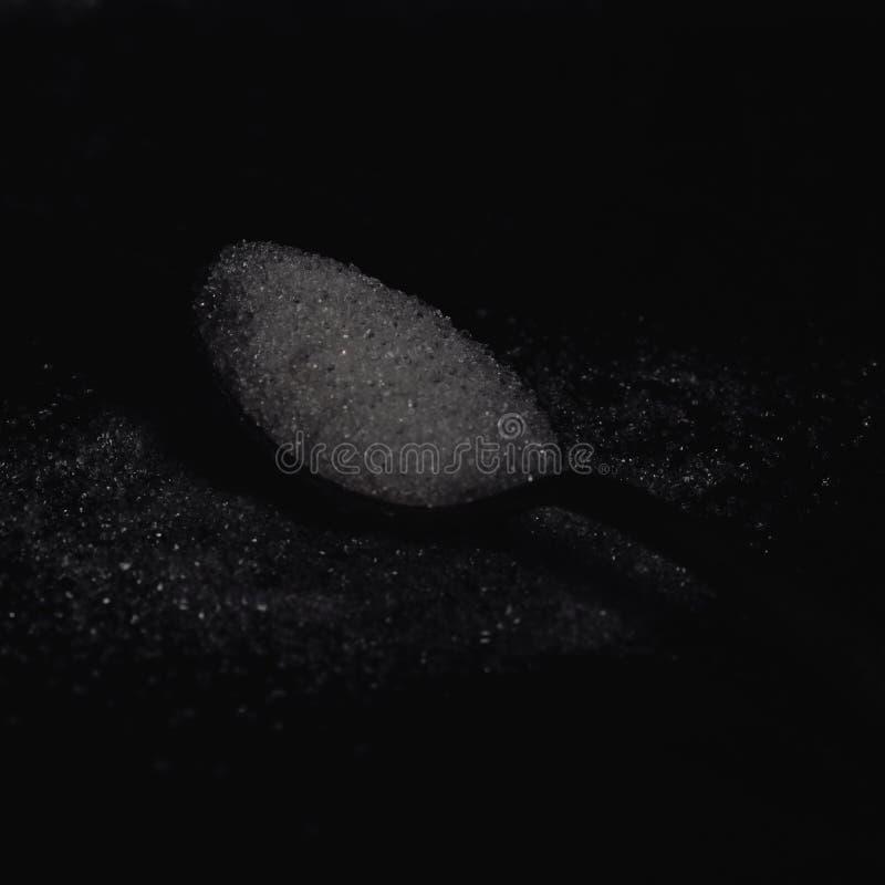 Dunkles Foto des Löffels mit raffiniertem Zucker auf dem dunklen Hintergrund, horizontale Ansicht, zurückhaltende Beleuchtung lizenzfreies stockbild