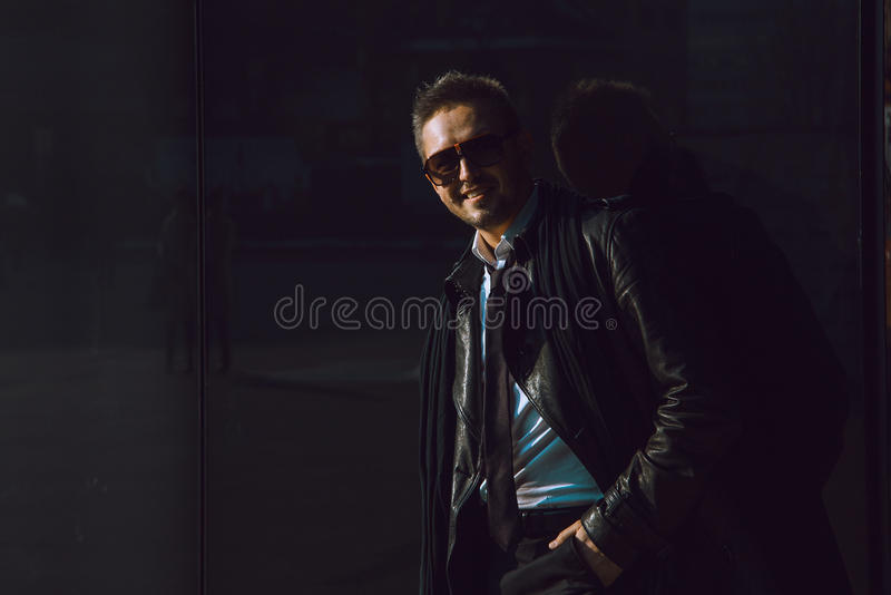 Dunkles Foto des SpaßGeschäftsmannes in ledernem Klagen- und Sonnenbrillene stockbild