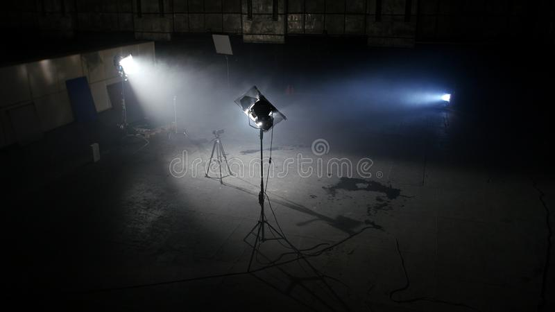 Dunkles Fotostudio mit hellen Scheinwerfern Geräumige Dunkelkammer mit gelieferten Flutlichtern und Kamera auf dem Stativ bereit  lizenzfreies stockfoto