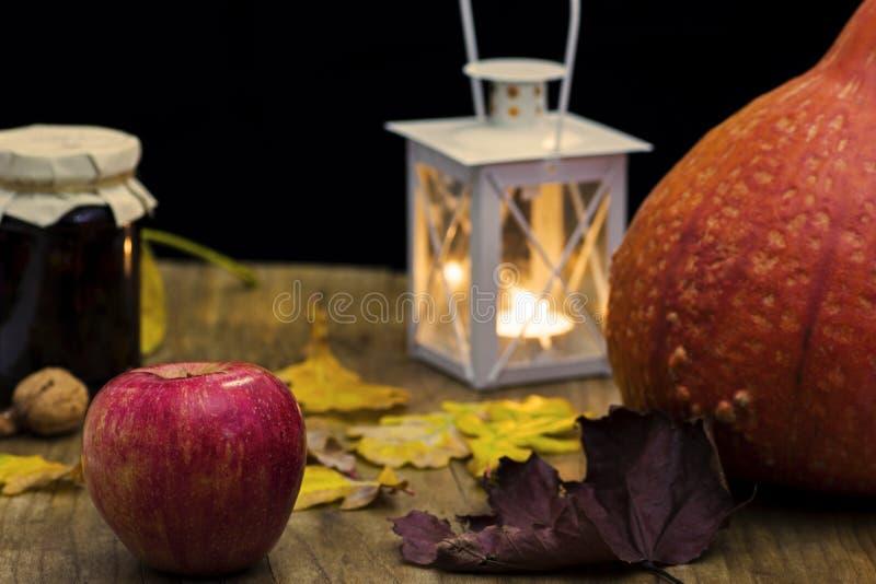 Dunkles Herbststillleben mit Kürbis, Kerze und Lampe, mit yello lizenzfreies stockfoto