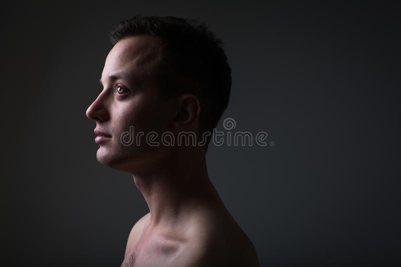 Dunkles Low-Key-Portrait eines jungen Mannes auf grauem Hintergrund lizenzfreie stockbilder