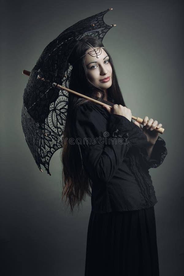 Dunkles Mädchen der Mode, das mit schwarzem Regenschirm aufwirft stockfotografie