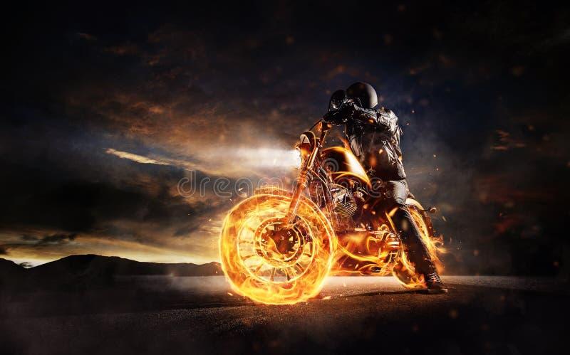 Dunkles motorbiker, das auf brennendem Motorrad im Sonnenunterganglicht bleibt lizenzfreie stockfotos