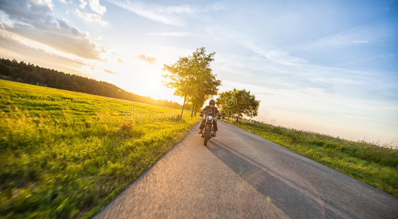 Dunkles Motorrad der motorbiker Reithohen leistung im Sonnenuntergang stockfotos