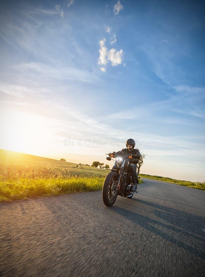Dunkles Motorrad der motorbiker Reithohen leistung im Sonnenuntergang lizenzfreies stockbild
