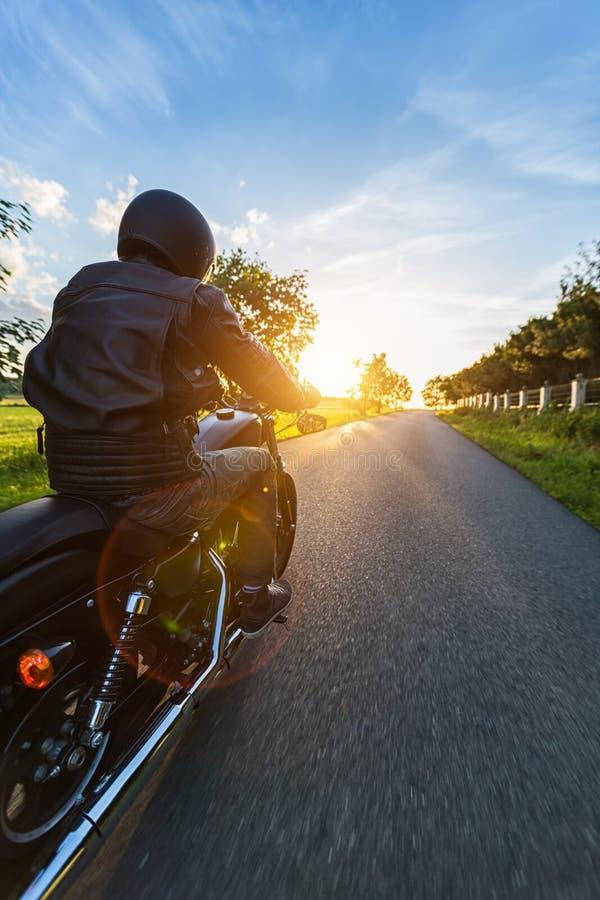 Dunkles Motorrad der motorbiker Reithohen leistung im Sonnenuntergang stockbilder