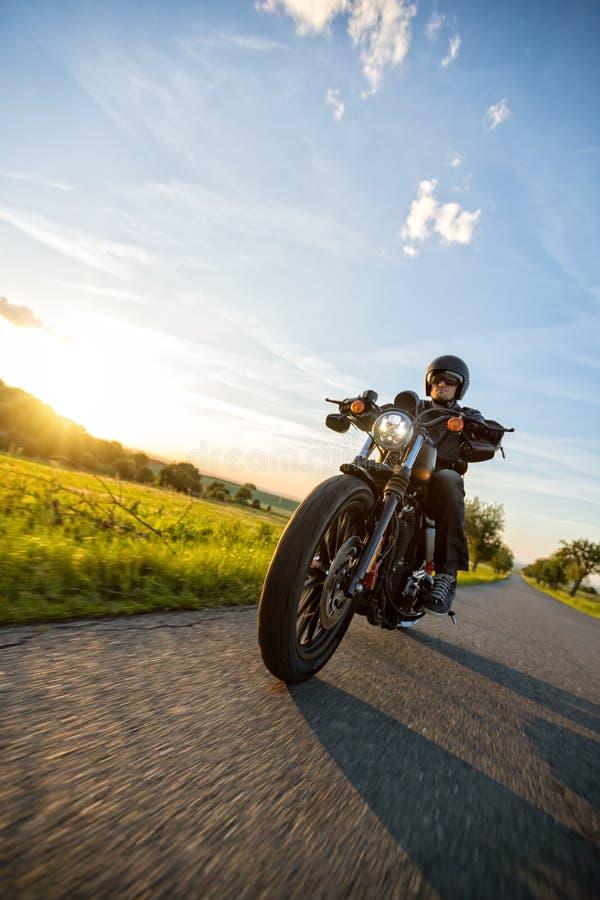 Dunkles Motorrad der motorbiker Reithohen leistung im Sonnenuntergang lizenzfreie stockbilder