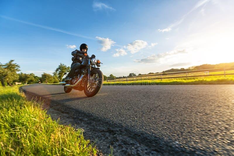 Dunkles Motorrad der motorbiker Reithohen leistung im Sonnenuntergang stockfotografie