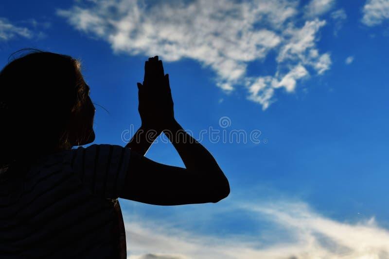 Dunkles Schattenbild von weiblichen Händen bei Sonnenuntergang im Himmel Die Palmen hoben zur Sonne an stockbild