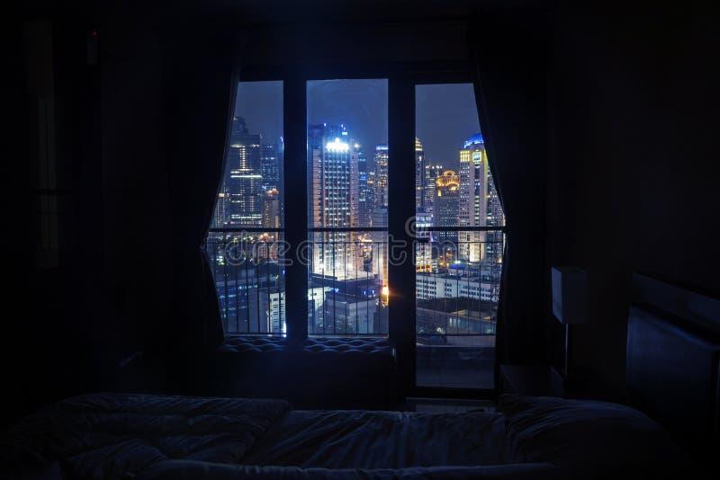 Dunkles Schlafzimmer mit Licht auf den Wolkenkratzern lizenzfreie stockbilder