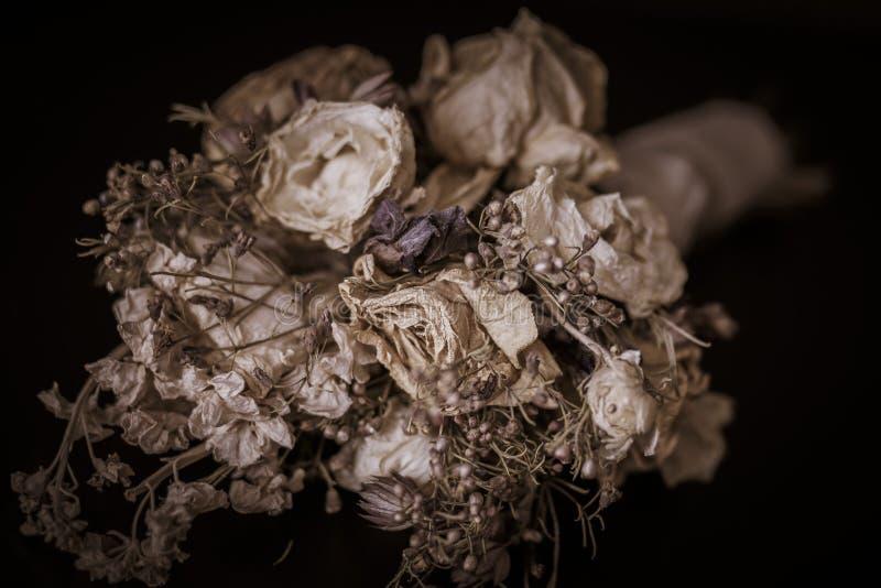 Dunkles schwermütiges Bild von weißen Rosen in einem Blumenstrauß stockfotografie