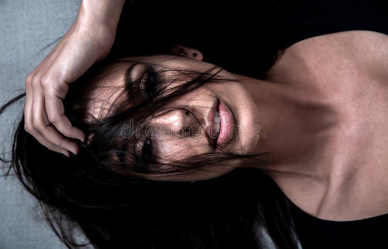 Dunkles Stimmungsportr?t einer Frau beim L?gen auf einem Sofa lizenzfreies stockbild