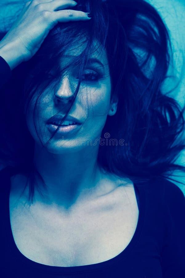 Dunkles Stimmungsportr?t einer Frau beim L?gen auf einem Sofa lizenzfreie stockfotografie