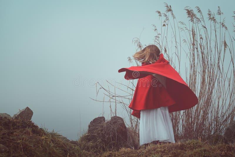Dunkles und surreales Porträt einer roten mit Kapuze Frau lizenzfreies stockfoto