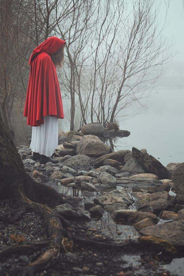 Dunkles und trauriges Porträt einer roten mit Kapuze Frau stockbilder