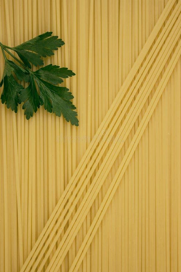 Dunne die deegwaren in rijen worden geschikt Gele Italiaanse deegwaren Lange spaghetti Dunne spaghetti Voedsel achtergrondconcept royalty-vrije stock afbeelding