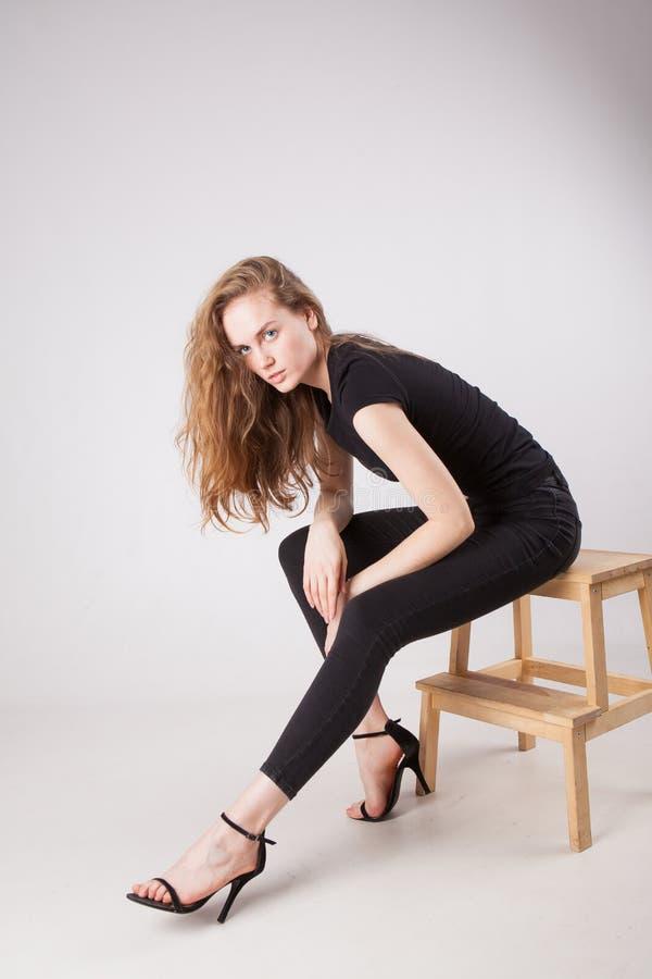Dunne jonge vrouw in zwarte kleren op een lichte achtergrond stock afbeelding