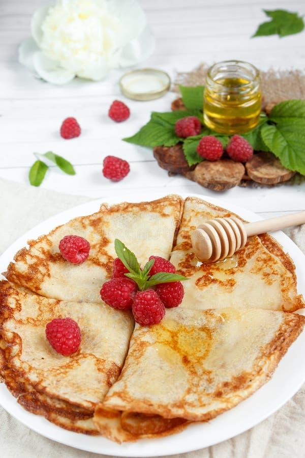 Dunne pannekoeken met honing en frambozen op een witte plaat stock afbeelding