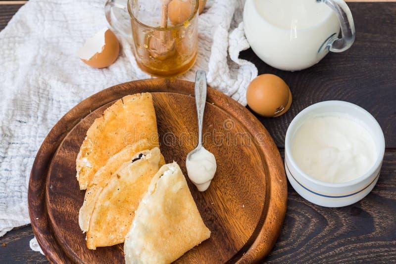 Dunne pannekoeken met kwark, gedroogde pruimen, honing en zure room stock afbeelding