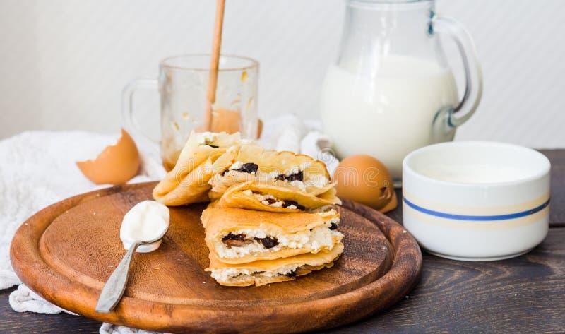 Dunne pannekoeken met kwark, gedroogde pruimen, honing en zure room royalty-vrije stock foto