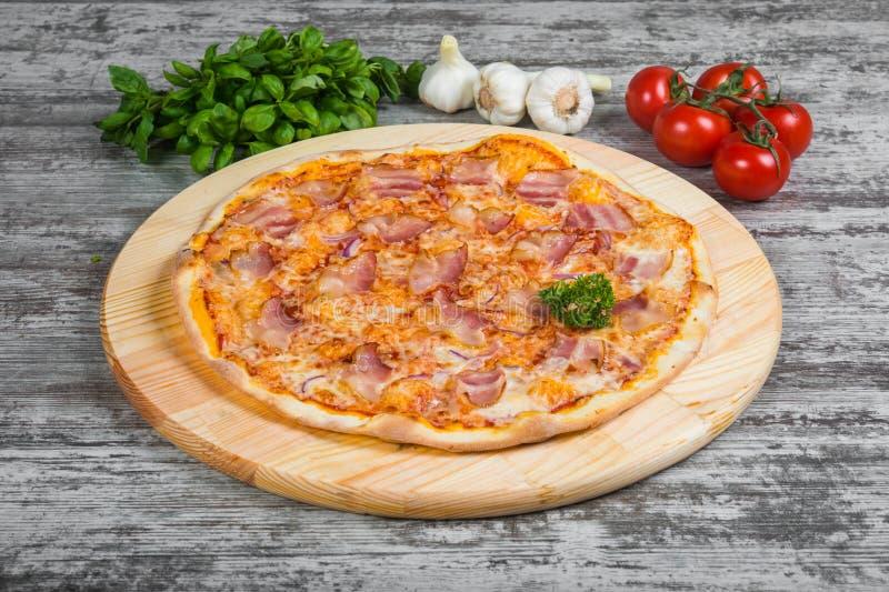 Dunne pizza met bacon en ui, rozemarijn en kruiden op een licht stock fotografie