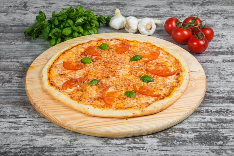Dunne pizza met tomaten en kaas, rozemarijn en kruiden op een lichte houten achtergrond royalty-vrije stock afbeeldingen