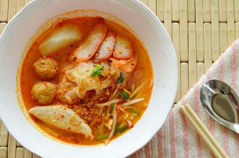 Dunne rijstnoedels die het varkensvlees van de plakbarbecue en garnalenbal in kruidige soep bedekken stock foto