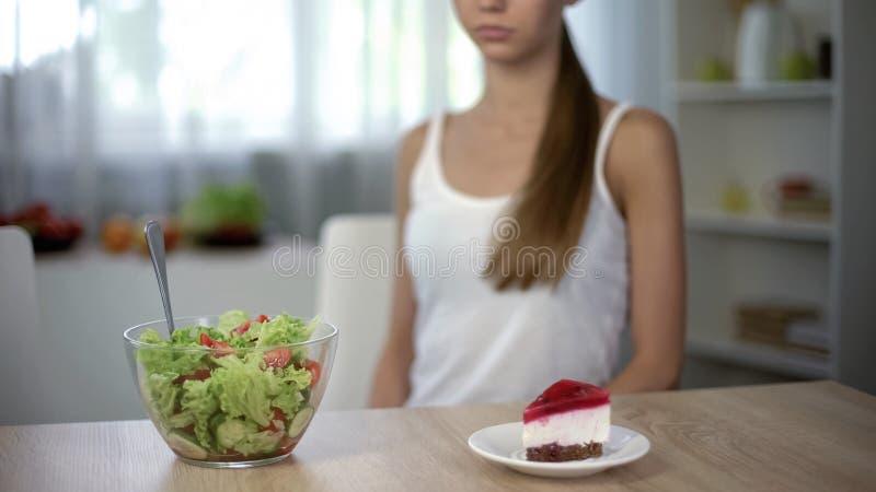 Dunne vrouw die tussen cake en salade, gezonde voeding versus hoog-calorievoedsel kiezen royalty-vrije stock foto's